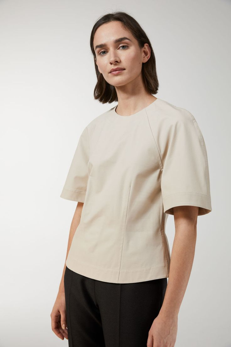 Cut from a stretchy cotton twill, this top has a crisp and sturdy feel. Designed in a slightly boxy fit with short, wide raglan-cut sleeves. Round neck wit