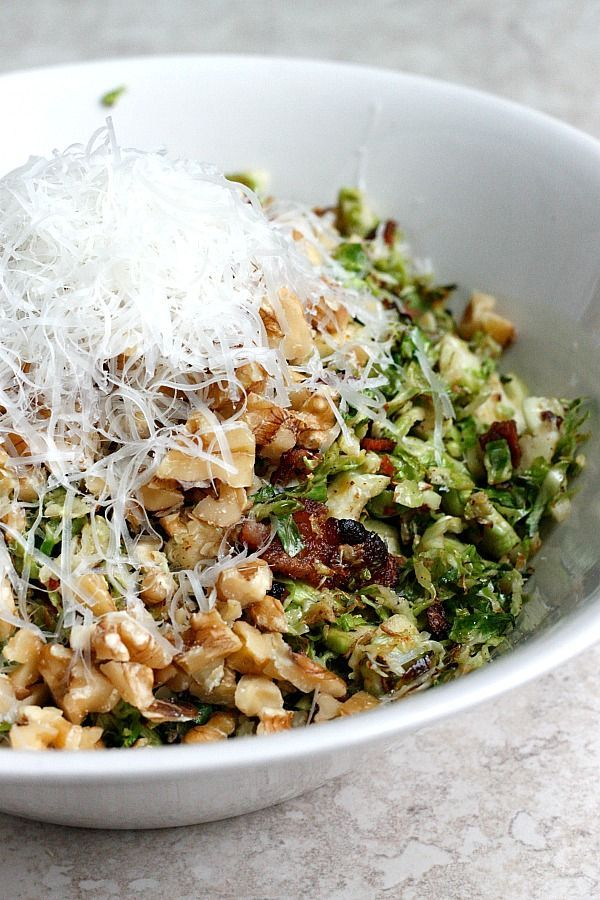 A warm bacon and brussels sprouts shredded salad tossed with chopped walnuts and fresh parmesan