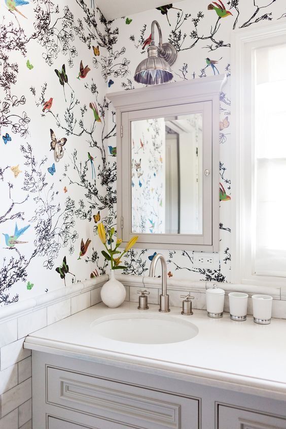 Butterfly wallpaper paired with white subway tile and white vanity creates a whimsical look in the bathroom.