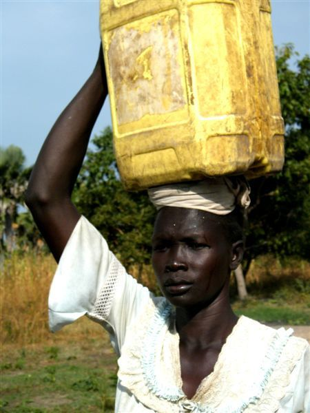 Sudan woman carries a heavy water container on her head