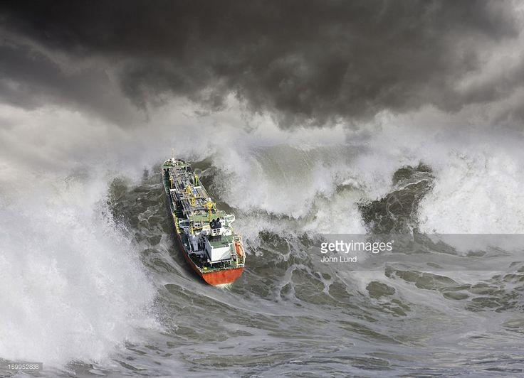 An oil tanker ship churns up a huge tsunami like wave in rough seas.