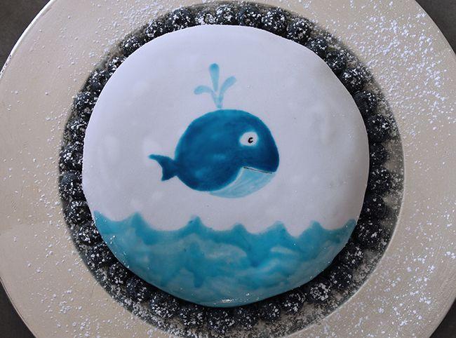 Kuchen mit gezeichnetem Fischmotiv. Bemalter Kuchen mit Lebensmittelfarbe. Schokoladenkuchen mit Blaubeeren.