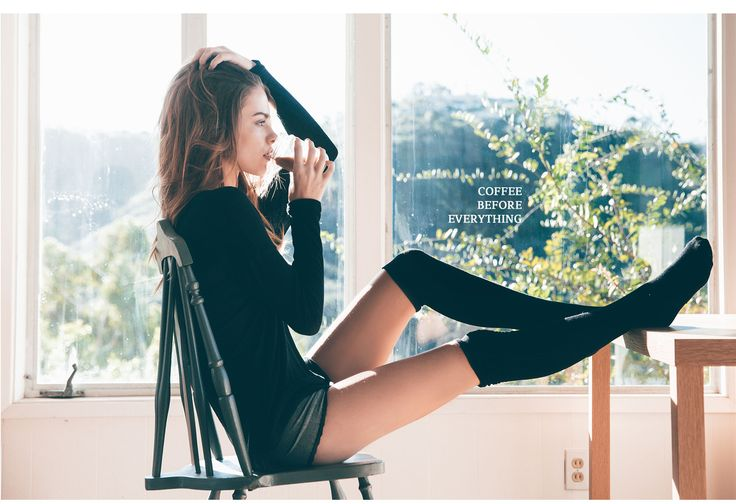 Easy days sitting in a chair drinking coffee. She is wearing a black sweater and black knee high socks from Tillys