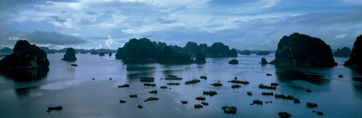 Groups of fishing boats dot the placid waters of marvelous Halong Bay in the extreme north of Vietnam. © Michael Yamashita