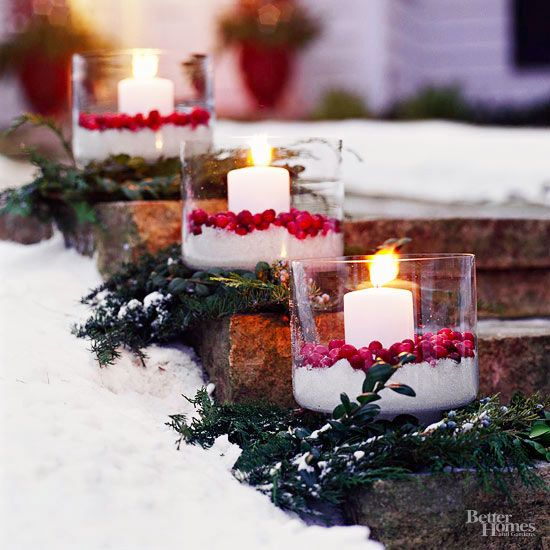 This inexpensive outdoor Christmas idea is a cinch to execute. Simply layer a stocky glass vase with faux snow and real cranberries (or fake, if you're worried about animals). Tuck in a pillar candle. Align on your walkway with fir bundles topped with your pretty luminarias.