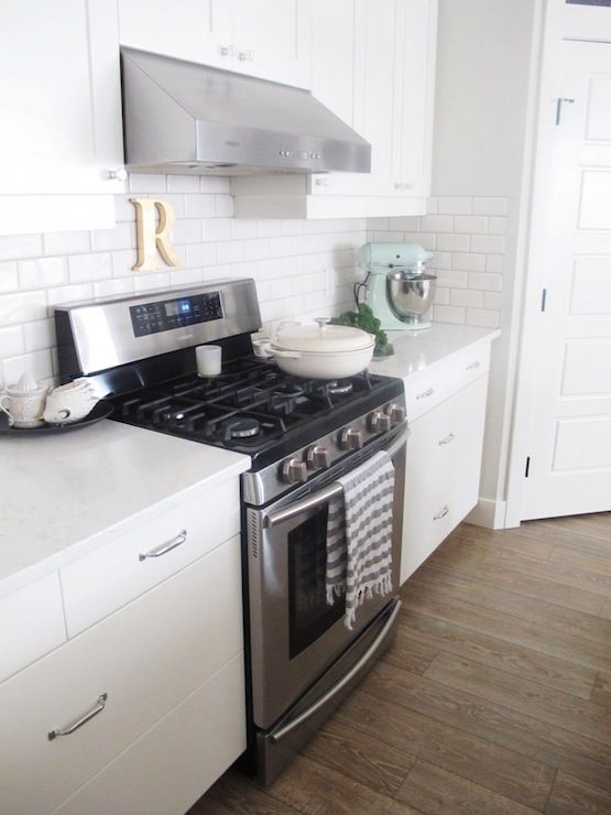 All white kitchen with flat front, lower cabinets framing the stainless steel range with white quartz counters topped with Anthropologie Hedgehog Measuring Cups paired with a subway tiled backsplash with shaker upper cabinets highlighting a stainless steel vent hood.