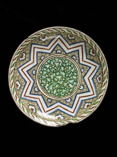 Dish Place of origin: Iznik, Turkey (made) Turkey Date: ca. 1585-1600 (made) Physical description Deep dish of glazed fritware. Decorated at the centre with green leaves, surrounded by star-shaped ornaments of red and blue parallel lines; black scrolls in the interspaces, with red and green border.