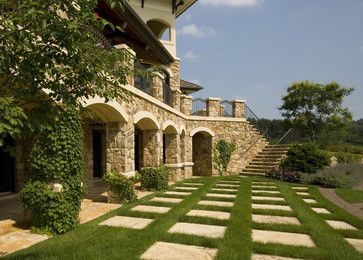 Large travertine stepping stones with grass joints. Ivy climbing along vertical stone walls.