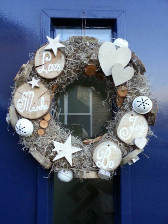 Winterkrans, gemaakt met stro krans, grijs gedroogd mos, plakjes van een tak, houten hartjes en sterren, belletjes en onze namen op plakjes hout geschilderd. Hoe makkelijk kan het zijn?!!