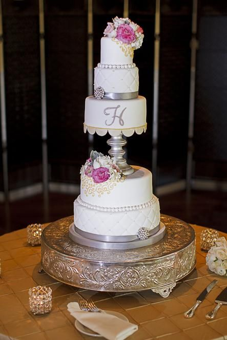 The unique wedding cake featured pink and cream colored flowers and silver metallic detailing. | Photos by Toby Tucker, Cake Goodness