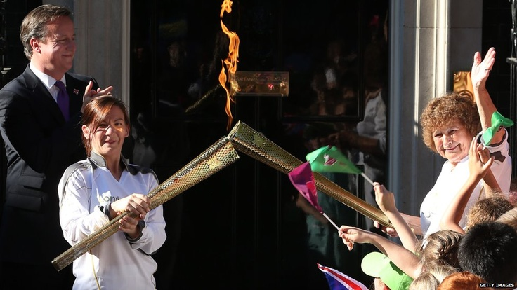 Prime Minister David Cameron looks on as Kate Nesbitt passes the flame on to Florence Rowe