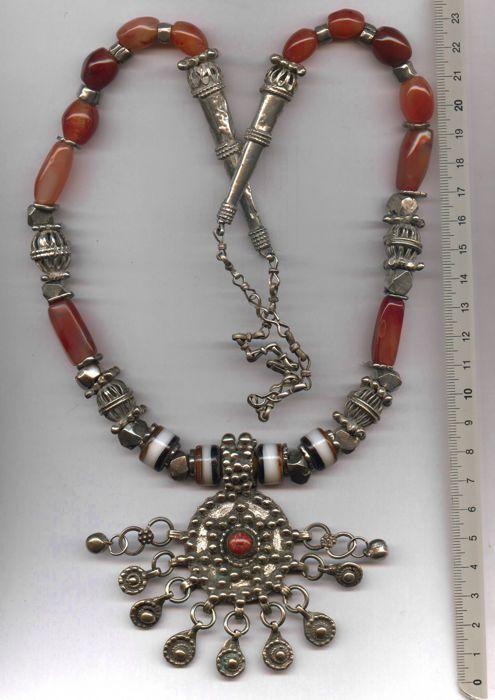 """Jemenitische halsketting met hanger van de munt  Deze ketting van Jemen is gemaakt van oud zilver glas en Agaat kralen. De oude hanger is gemaakt van een oude Schijfzalm met een klein stukje rood koraal als een cabochon. Er zijn grote korrels van zilver vastgesoldeerd aan de muntDe zilversmid gebruikt deze meer dan honderd jaar oude munt handel uit """"Verenigd Koninkrijk Groot-Brittannië"""". Deze munten werden gebruikt voor de handel in Hong Kong en China. De datum van de munt is 1913 de 3 van…"""
