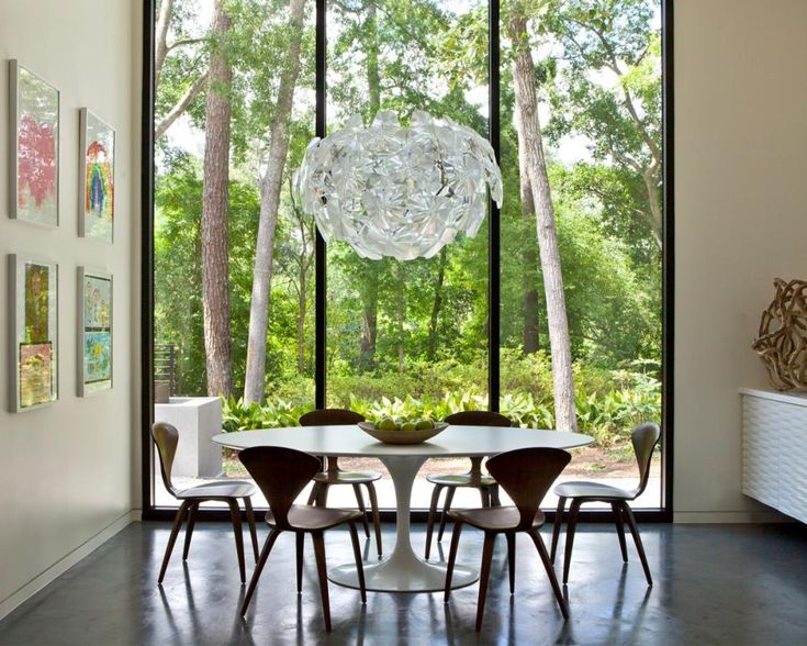 Floor-to-ceiling windows allows natural light to illuminate this midcentury modern dining room with a round white table and brown wooden chairs. A polished concrete floor offers an updated look, while framed kids' artwork adds a lively touch.