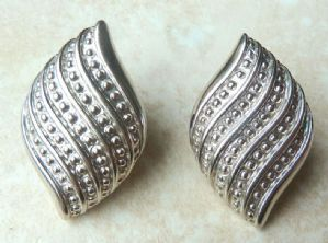 A Vintage large pair of Napier feather style swirl earrings in silver tone metal, with a raised embossed dot pattern.