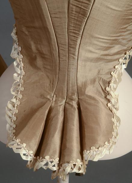 Auction House Coutau-Bégarie - Rare caraco à laPierrot, vers 1785-1790, en taffetas vert bronze agrémenté dentrelacs de fins rubans crème, dos baleiné à basques retroussées. Décolleté carré, le devant baleiné est fermé par un laçage croisé destiné à laisser paraître le gilet ou corset choisi dans une couleur différente. La partie haute est composée de deux compères fermés par 3 boutons recouverts. Manches longues ajustées aux poignets fermées par 3 boutons recouverts, (état suberbe).