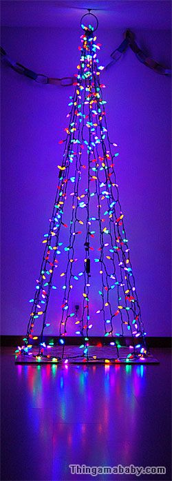 Photo of a cone-shaped string of Christmas lights running from floor to ceiling, aglow ...