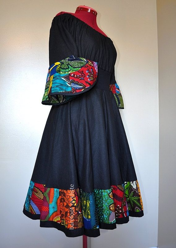 Dance With the Night – Swirly black dress with bold afritude...    • One-of-a-kind, figure-flattering bohemian gown; made from a medium-weight, black linen-cotton fabric, along with several bold African cotton prints at the hem.    • The top has below-elbow-length sleeves and elasticized neckline designed to sit off the shoulders. The sleeves have vibrant flare; they end with bright african patchwork, trimmed with a slim black trim.  The midriff is made from a black, soft cotton-blend…