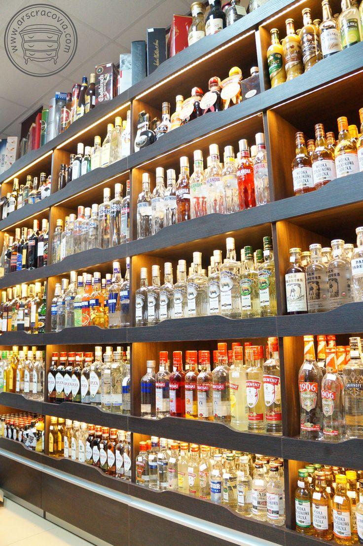 Wyposażenie sklepu spożywczego: wbudowane regały na alkohol z oświetleniem, z dolnymi szufladami, wykonane z płyt meblowych i laminatów HPL.