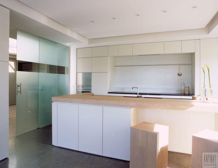 Gezandstraalde schuifdeuren op maat in een moderne keuken. Dubbele schuifdeur uitgevoerd in gezandstraald glas met motief, aluminium rail (weggewerkt in vals plafond) en inox grepen. Op maat gemaakt door Anyway Doors.