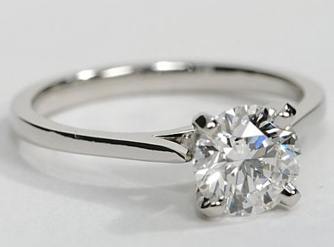 Elegant, simple platinum solitaire engagement ring with a thin band to make your center diamond stand out. You can choose a diamond of any shape and size to set in this ring.