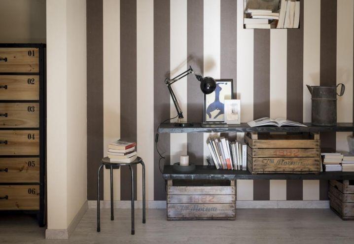 Una parete del living dipinta a strisce verticali colore crema e marrone scuro, con un effetto caldo e accogliente. Il proprietario del monolocale ha scelto arredi su misura, a partire dalle scaffalature, arricchite da complementi in ferro e acciaio a creare un clima industriale
