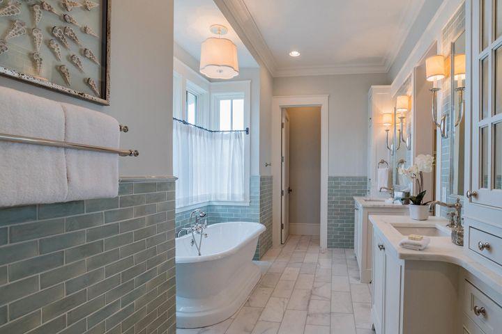 coastal bathroom with soaking tub and aqua subway tile