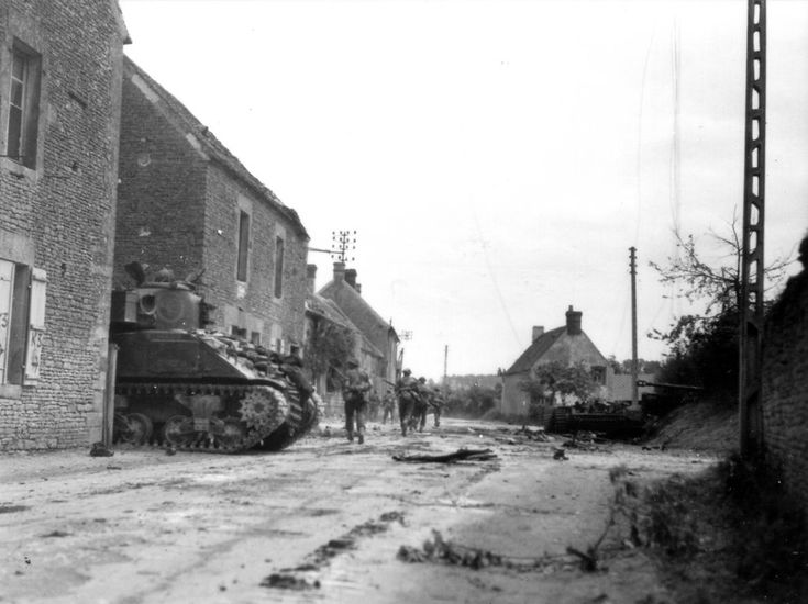 A Sherman of The South Alberta Regiment, 4th Canadian Armoured Division pokes its nose out from cover in St. Lambert-Sur-Dives, France, Aug 19, 1944. They were right to be cautious, to the right of the picture on the right hand side of the road rest the remains of a German Tiger tank. It has suffered a massive internal explosion that has blown its turret into the hedgerow, with only the gun tube visible. As late as 1975 parts of this Tiger were being found in the hedgerow by collectors.