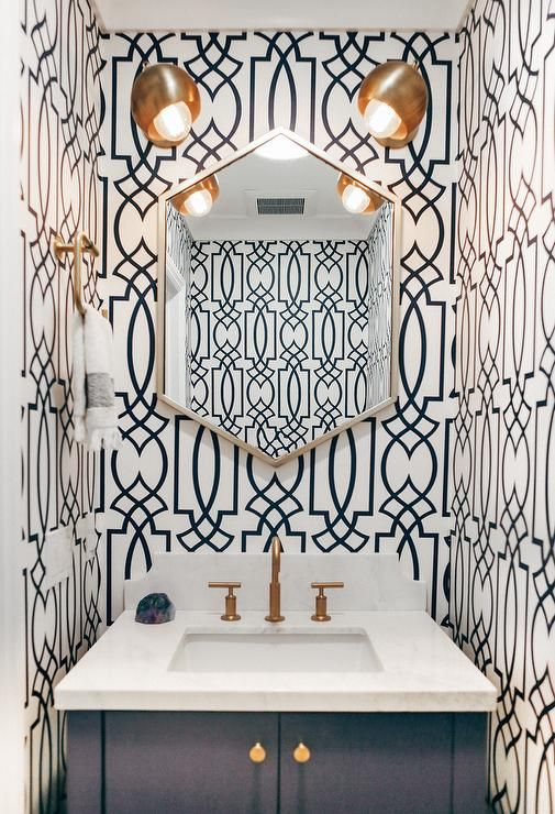 White and navy blue powder room features walls clad in blue trellis wallpaper, Antonina Vella Dolce Vita Wallpaper in Navy Blue, lined with a silver geometric mirror, illuminated by brass sconces placed over a navy blue washstand adorned with gold hex knobs and a marble counter and backsplash.