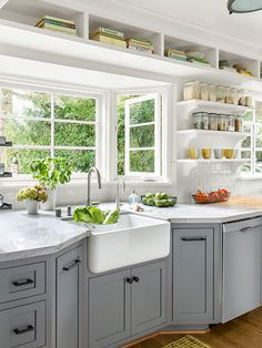 The kitchen redo of this 1940s California bungalow included moving the sink to a new home in an existing bay with all-new windows for front-yard views. Open shelves and storage cubbies keep the space feeling airy and bright.