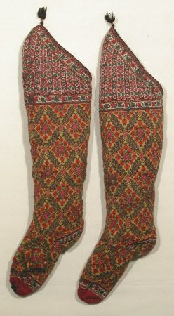 19 c. A pair of knitted wool socks from Persia. The toe is claret, the main part is lemon yellow ground with blue/ black/ shades of red. The knee has a cream ground with black/ reds/ green. They are lined with knitted wool. There is a narrow edging of interwoven silk in pink and black with silk cored silver thread with a black tassel. NT 1349256.1 and 2. Similar to a pair in Indianapolis Museum of Art 16.1117 a and b. (male). Snowshill Manor © National Trust / Richard Blakey.