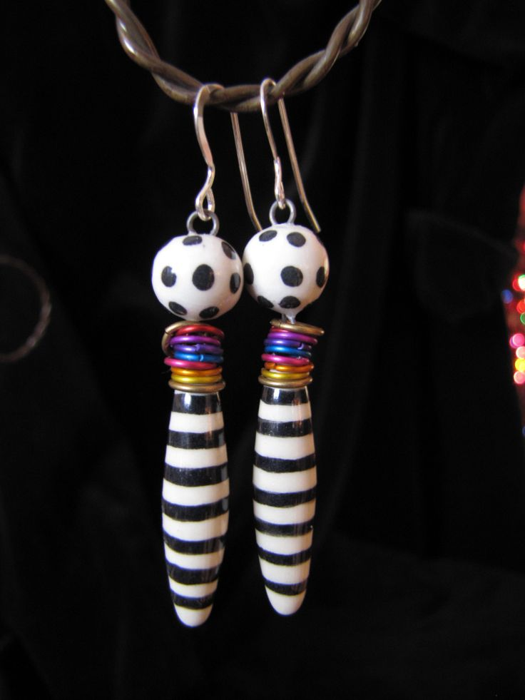 Earrings are made using a small bead with high fire wire imbedded and fired into the clay then connected to a larger Rice Bead. Anodized Aluminum Jumprings are added for a splash of color. Earwires are Sterling Silver.  http://claybuttons.com/Jewelry/ClayEarrings.html