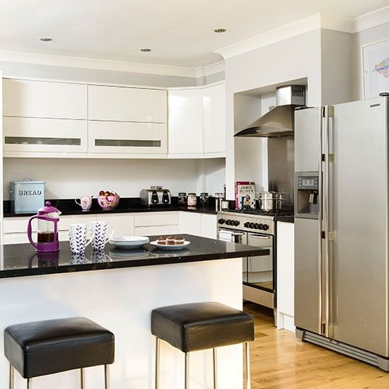 This contemporary kitchen with black granite worktops has a breakfast bar and stools, providing somewhere casual to sit and eat.