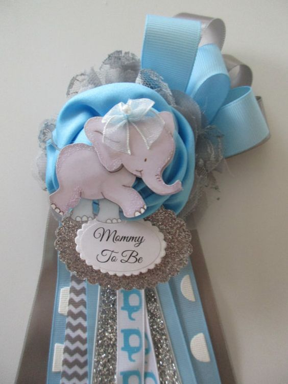 Mom or Grandma To Be Elephant Baby Shower Corsage. Perfect for that Special Mom or Grandma To Be. Comes with a Brooch style pin. Made with satin, chiffon and lace flower, pretty ribbon and lace, elephant embellishment, and name tag. Also available for baby girl shown in pic 4. Will ship in 5-7 business days. If you need sooner, please let m know. Can customize to any theme, just ask. Can be made for a baby boy too! Can be made in other colors, please ask. Corsage is 4 x8 inches.