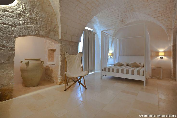 Masseria Grottone, un gîte rural d'exception en Italie : ici la chambre est aménagée dans une pièce au plafond en arcs voutés. Le lit à baldaquin donne un côté romantique aux lieux.