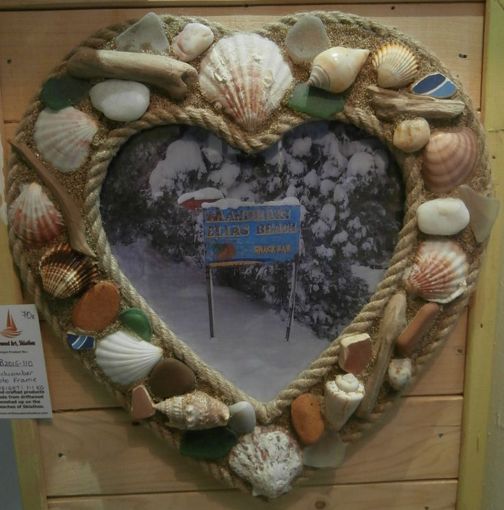 A real beachcomber themed heart-shaped photo frame.  Full of pretty beach fings including seaglass, shells, ceramic pieces, driftwood and sand.  Two pieces of rope have been applied around the outer and inner edges of the frame to finish it off beautifully.  A piece of plyboard backing has been fixed to the reverse by way of a couple of tiny screws - so when you want to change the photo you simply unscrew them and put in your favourite image.