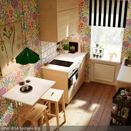 Die flippige Tapete mit buntem Blumen-Motiv dominiert die kleine Küche und verleiht ihr so Dynamik. Die Gardine ist schwarz-weiß gestreift und setzt…