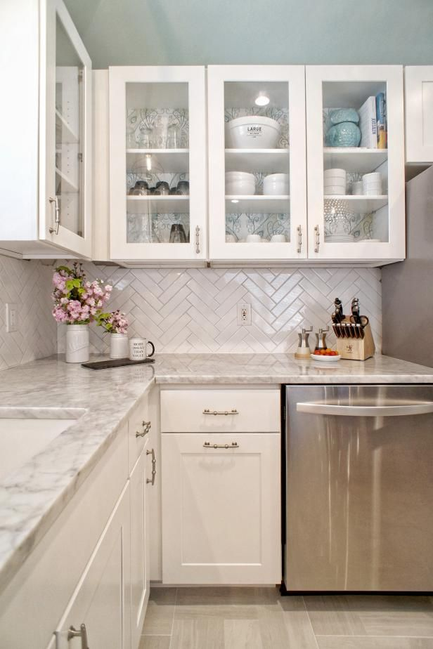 HGTV invites you to take a look at this white and gray modern kitchen with a white tile herringbone backslash, glass front cabinets, and marble countertops.