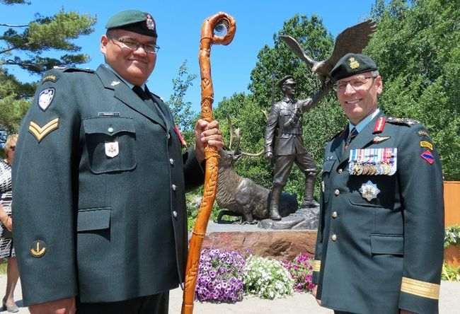 Corporal Paul Nakogee of the Algonquin Regiment, holds the regiment's eagle staff with Lieutenant-General Marquis Hainse, commander of the Canadian Army, after a statue honouring Sgt. Francis Pegahmagabow, Canada's most highly decorated indigenous soldier, was unveiled in Parry Sound on National Aboriginal Day. Sgt. Peter Moon/Canadian Rangers