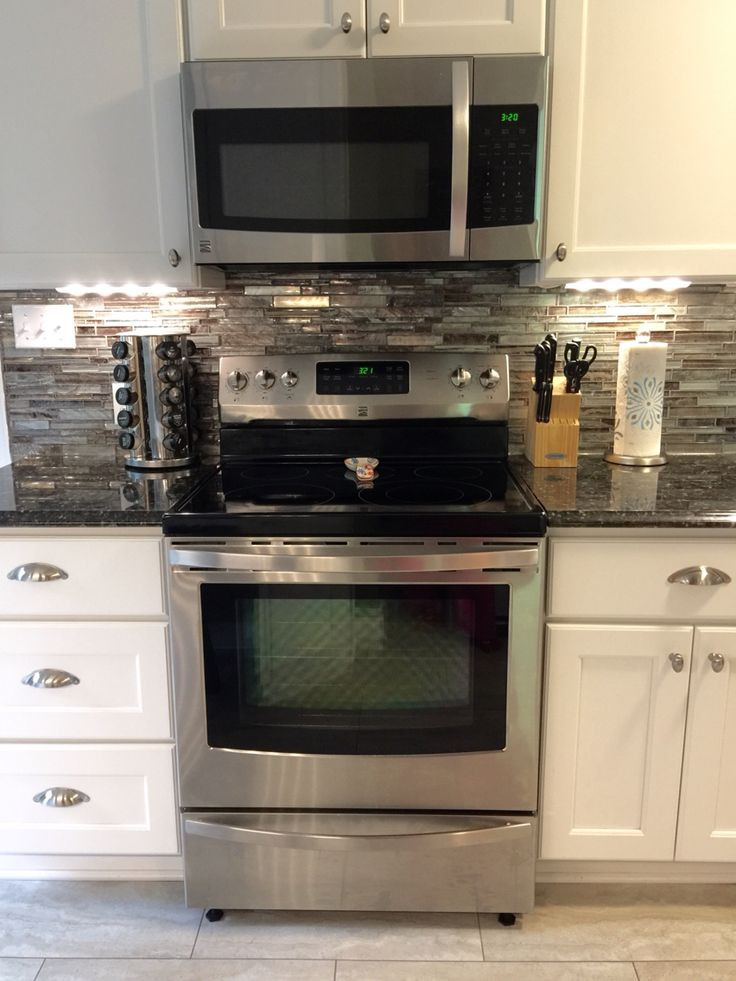 My beautiful kitchen renovation with Allen Roth Shimmering Lights glass backsplash (from Lowes), white cabinets, and dark butterfly black granite countertops.
