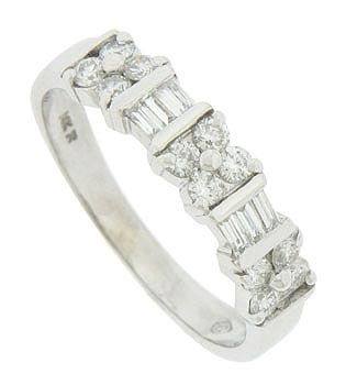 Dazzling round and baguette cut diamonds adorn the face of this 14K white gold wedding band. The fine faceted diamonds are set in a pattern of floral quartets separated by pairs of vertically set baguettes. The distinctive setting features elongated prongs and bold milgrain to bring added drama and sparkle to this spectacular wedding ring. The estate ring measures 4.67 mm in width. Circa: 1950. Size 9. We can re-size.