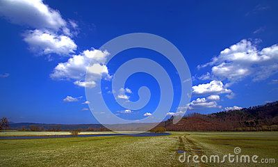Spring sky above a green meadow crossed by a small river. The clouds appear to outline a path, a celestial path.