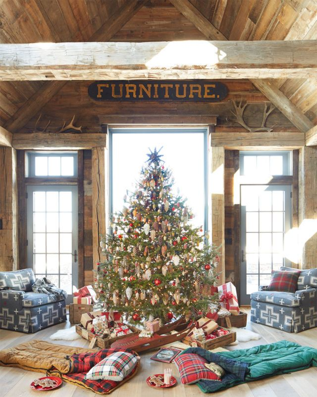 """Sleeping bags for """"campouts"""" turn this Christmas tree into a hot spot for an at-home holiday getaway.   - CountryLiving.com"""
