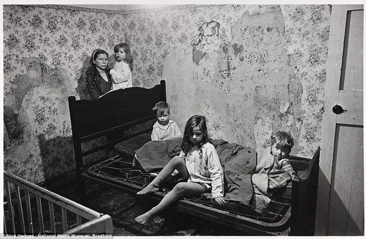 Mrs M huddles with her four young children in the council house that they share with her husband in Balsall Heath, Birmingham. Their home has no bathroom, no hot water and the inside walls are running with damp. The children slept on sodden seat cushions covered by a couple of old 'macs'. They are pictured in January 1969, when a thick layer of snow lay outside and the windows were broken