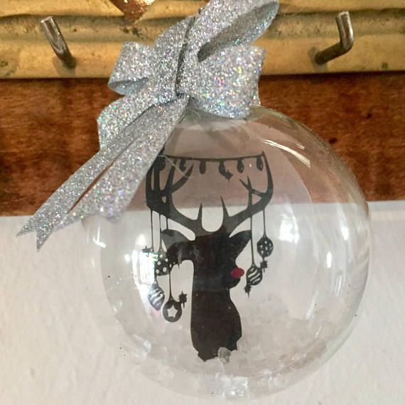 This 60mm handmade floating Adorned Reindeer Silhouette glass ball ornament features a reindeer silhouette that is visible from both sides. His cute red nose will certainly lead Santa to your Christmas tree! The ornament is filled with artificial snow and topped with glittered