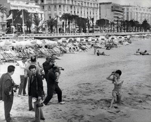 Straat-, strandfotografie. Fotografen filmen en fotograferen een jongedame in bikini met een fototoestel op het strand van Cannes, Frankrijk 1963. Het Filmfestival van Cannes.