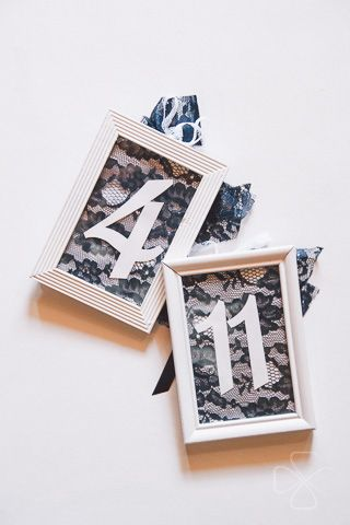 The table numbers were enclosed in white wooden frames and decorated with black lace fabric.