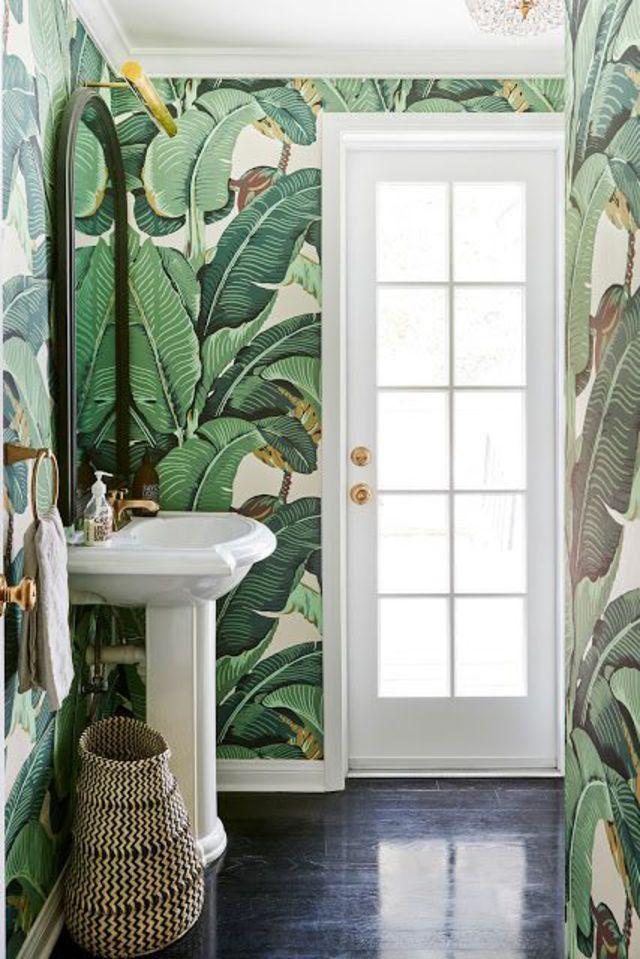 Une salle de bains à l'esprit jungle avec un papier peint à la végétation luxuriante