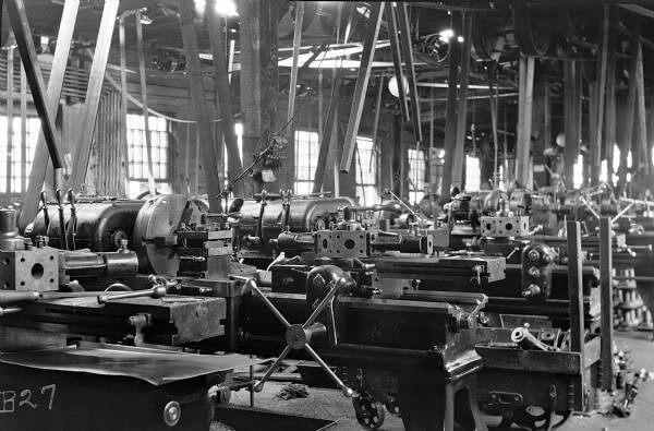 "View of new turret lathe (center) manufactured by American Tool Works. It is standing on a factory floor flanked by other similar machines that are attached to rotary belts, suspended from the ceiling. Electrical light bulbs are strung above each work station. The factory room is lit by both natural light from the windows and electricity. The original envelope housing this photograph was inscribed with the following information: ""They [the lathes] have a stop for cross carriage, same as ..."
