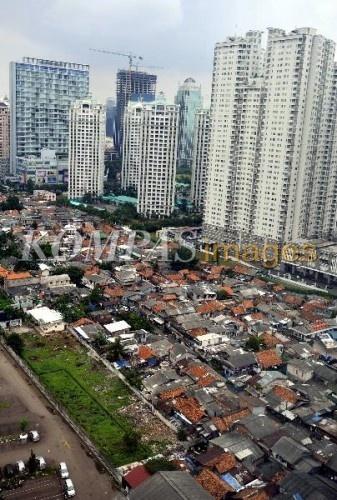 Kekurangan Ruang Terbuka Hijau  Permukiman padat penduduk berhimpitan dengan gedung-gedung perkantoran, apartemen, dan hotel di kawasan Jalan Sudirman, Jakarta, Sabtu (11/2/2012). pertumbuhan pembangunan gedung selam ini tak diimbangi pengadaan ruang terbuka hijau. Luas ruang terbuka hijau yang hanya 9,8 persen dari luas kota Jakarta masih jauh dari luas ideal sekitar 30 persen.
