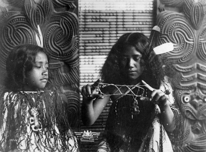 Two Maori girls dressed in korowai (tag cloaks), with tiki around their necks and feathers in their hair. One is playing whai (string games). Photograph taken by the New Zealand Government Tourist Department circa 1900.